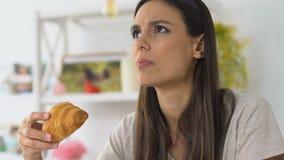 Δάγκωμα κοριτσιών croissant και αίσθημα της δυσάρεστης ευαισθησίας πόνου, δοντιών και γόμμας απόθεμα βίντεο
