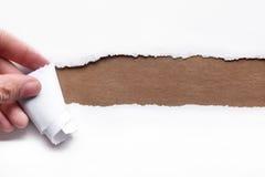 Δάκρυ χεριών μια λουρίδα του εγγράφου στοκ φωτογραφία