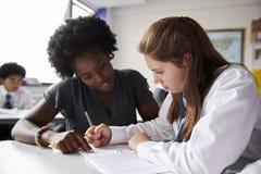 Δάσκαλος γυμνασίου που δίνει τη γυναίκα σπουδαστή που φορά ομοιόμορφη μια έως μια εκπαίδευση στο γραφείο στοκ εικόνες