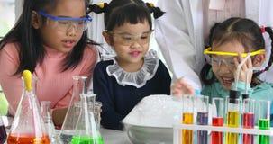 Δάσκαλος επιστημών και ασιατικοί σπουδαστές που εξετάζουν το κύπελλο που σκάει τη φυσαλίδα φιλμ μικρού μήκους