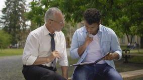 Δάσκαλος και έξυπνος ισπανικός σπουδαστής που συζητούν το πρόγραμμα επιστήμης κοντά στο πανεπιστήμιο απόθεμα βίντεο