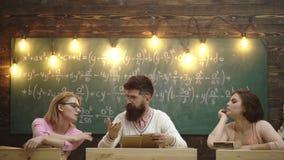 Δάσκαλος και δύο γυναίκες σπουδαστές που συζητούν στο υπόβαθρο του πράσινου πίνακα στον οποίο οι τύποι γράφονται Διαδικασία εκμάθ απόθεμα βίντεο
