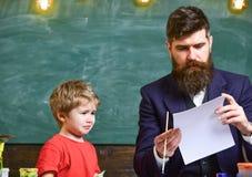 Δάσκαλος και παιδί στην τάξη με τον πίνακα κιμωλίας στο υπόβαθρο Οικογένεια στα πολυάσχολα πρόσωπα που δημιουργούν, σχεδιασμός Πα στοκ φωτογραφίες