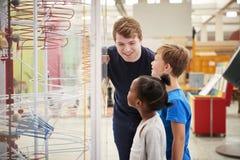 Δάσκαλος και παιδιά που μιλούν για ένα έκθεμα επιστήμης στοκ εικόνες