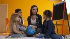 Δάσκαλος και παιδιά που συζητούν τη σφαίρα στον παιδικό σταθμό φιλμ μικρού μήκους