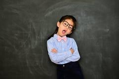 Δάσκαλος κοριτσιών παιδιών που στέκεται στο υπόβαθρο πινάκων Στοκ Φωτογραφία