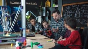 Δάσκαλος με τα παιδιά που ερευνούν την τρισδιάστατη εκτύπωση