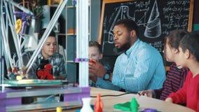 Δάσκαλος με τα παιδιά που ερευνούν την τρισδιάστατη εκτύπωση απόθεμα βίντεο