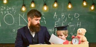 Δάσκαλος, πατέρας που ελέγχει την εργασία, βοήθειες στο αγόρι, γιος Μεμονωμένη έννοια μελέτης Πολυάσχολο παιδί που μελετά στο σχο Στοκ εικόνα με δικαίωμα ελεύθερης χρήσης