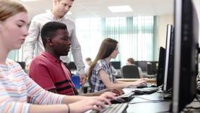 Δάσκαλος που βοηθά την αρσενική εργασία σπουδαστών γυμνασίου στην κατηγορία υπολογιστών φιλμ μικρού μήκους