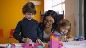 Δάσκαλος που βοηθά την κατηγορία προσχολικών παιδιών για να σύρει