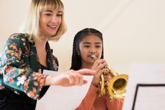 Δάσκαλος που βοηθά τη γυναίκα σπουδαστή για να παίξει τη σάλπιγγα στο μάθημα μουσικής στοκ εικόνες με δικαίωμα ελεύθερης χρήσης