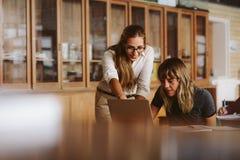 Δάσκαλος που βοηθά τη γυναίκα σπουδαστή στη μελέτη Στοκ εικόνα με δικαίωμα ελεύθερης χρήσης