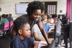 Δάσκαλος που βοηθά τη θηλυκή γραμμή μαθητών σπουδαστών γυμνασίου που εργάζονται στις οθόνες στην κατηγορία υπολογιστών στοκ φωτογραφία