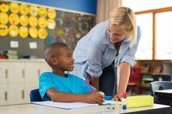 Δάσκαλος που βοηθά το αγόρι με την εργασία Στοκ Εικόνα