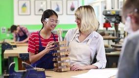 Δάσκαλος που βοηθά το θηλυκό σπουδαστή γυμνασίου φιλμ μικρού μήκους