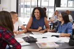 Δάσκαλος που μελετά τα σχολικά βιβλία στην κατηγορία με τα παιδιά γυμνασίου Στοκ Εικόνες