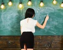 Δάσκαλος των μαθηματικών που γράφει στον πίνακα κιμωλίας, οπισθοσκόπος Γυναικείος προκλητικός δάσκαλος στην κοντή φούστα με τη σχ Στοκ Φωτογραφία