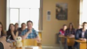 Δάσκαλος με μια ομάδα σπουδαστών γυμνασίου στην τάξη Άποψη από τα χέρια του δασκάλου που εξηγεί τη διάλεξη απόθεμα βίντεο