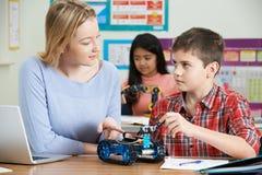 Δάσκαλος με τους μαθητές στο μάθημα επιστήμης που μελετούν τη ρομποτική στοκ φωτογραφίες