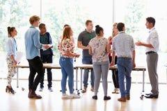 Δάσκαλος με τους φοιτητές πανεπιστημίου που υπερασπίζονται τα γραφεία στην τάξη Στοκ εικόνες με δικαίωμα ελεύθερης χρήσης