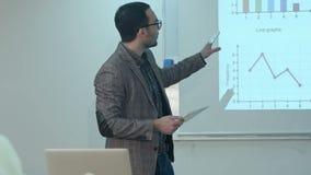 Δάσκαλος που δίνει το μάθημα στους σπουδαστές που χρησιμοποιούν την ψηφιακή ταμπλέτα στην τάξη απόθεμα βίντεο