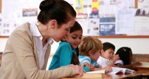 Δάσκαλος που βοηθά ένα μικρό κορίτσι με την ανάγνωση κατά τη διάρκεια της κατηγορίας απόθεμα βίντεο