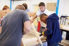 Δάσκαλος που βοηθά τους φοιτητές πανεπιστημίου που μελετούν την ξυλουργική στοκ φωτογραφία