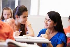 Δάσκαλος που βοηθά το θηλυκό σπουδαστή γυμνασίου στην τάξη Στοκ Εικόνες