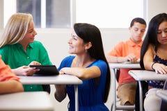 Δάσκαλος που βοηθά το θηλυκό σπουδαστή γυμνασίου στην τάξη στοκ φωτογραφίες