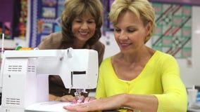 Δάσκαλος που παρουσιάζει γυναίκα πώς να ράψει τη χρησιμοποίηση της ηλεκτρικής μηχανής απόθεμα βίντεο