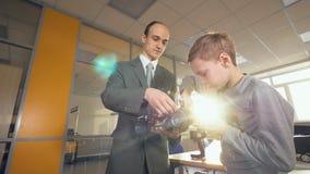 Δάσκαλος που παρουσιάζει στο σχολικό σπουδαστή φιλικό προς το περιβάλλον μελλοντικό αυτοκίνητο Ηλεκτρονικός, υδρογόνο, ιονικό αυτ φιλμ μικρού μήκους