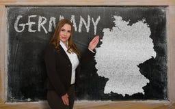 Δάσκαλος που παρουσιάζει χάρτη της Γερμανίας στον πίνακα Στοκ Φωτογραφία