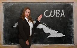 Δάσκαλος που παρουσιάζει χάρτη της Κούβας στον πίνακα Στοκ Φωτογραφία