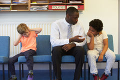 Δάσκαλος που λύνει το πρόβλημα μεταξύ δύο σχολικών σπουδαστών στοκ εικόνες
