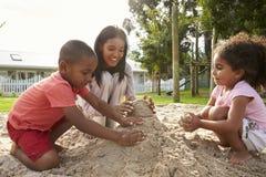 Δάσκαλος στο σχολικό παιχνίδι Montessori με τα παιδιά στο κοίλωμα άμμου στοκ εικόνες με δικαίωμα ελεύθερης χρήσης