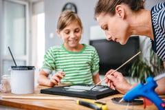 Δάσκαλος τέχνης που βοηθά έναν σπουδαστή με τη ζωγραφική Στοκ Εικόνες