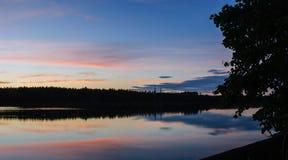 Δάσος από τη λίμνη, ενάντια στο σκηνικό του ηλιοβασιλέματος Στοκ φωτογραφία με δικαίωμα ελεύθερης χρήσης