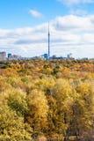 Δάσος και πόλη φθινοπώρου με τον πύργο TV στον ορίζοντα Στοκ Εικόνα