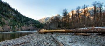 Δάσος όχθεων ποταμού με τα βουνά χιονιού Στοκ εικόνα με δικαίωμα ελεύθερης χρήσης