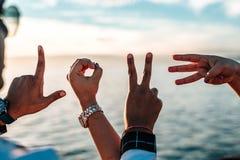 Δάχτυλα μιας ομάδας φίλων που διαμορφώνει τις επιστολές που συλλαβίζουν στοκ εικόνες
