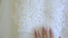 Δάχτυλα νυφών ήπια σε ένα γαμήλιο φόρεμα απόθεμα βίντεο