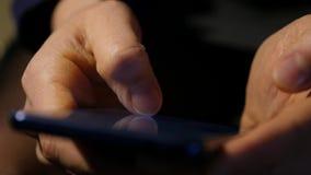 Δάχτυλα της γυναίκας κινηματογραφήσεων σε πρώτο πλάνο σε μια οθόνη επαφής του smartphone η γυναίκα χρησιμοποιεί ένα κινητό τηλέφω φιλμ μικρού μήκους