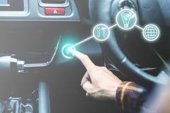 δάχτυλο που πιέζει το κουμπί μηχανών έναρξης/στάσεων στο αυτοκίνητο με την επιχείρηση Στοκ Φωτογραφίες