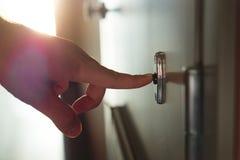 Δάχτυλο που πιέζει doorbell στην ηλιόλουστη πολυκατοικία στοκ φωτογραφία