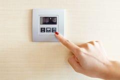 Δάχτυλο Womans στον έλεγχο διακοπτών κλιματιστικών μηχανημάτων Στοκ Φωτογραφίες
