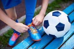 Δένοντας δαντέλλες ποδοσφαίρου ποδοσφαίρου αγοριών των μποτών στον πάγκο Στοκ Εικόνες