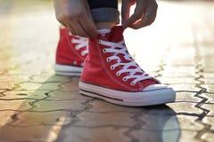 Δένοντας δαντέλλες στα πάνινα παπούτσια στο πάρκο Στοκ φωτογραφία με δικαίωμα ελεύθερης χρήσης