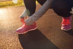 Δένοντας δαντέλλες παπουτσιών γυναικών Δρομέας στο θερινό πάρκο Στοκ Εικόνες