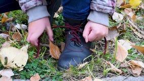 Δένοντας κορδόνια με τα χέρια παιδιών ` s υπαίθρια το φθινόπωρο φιλμ μικρού μήκους